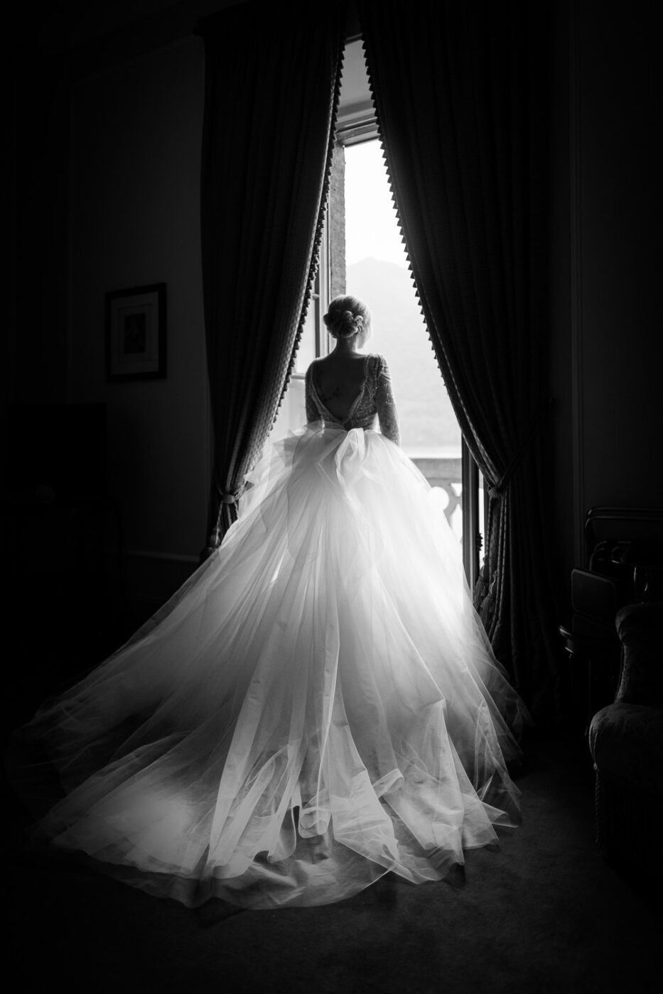 Black and white portrait of a bride from behind looking through the window to Lake Como in Italy at Villa Pizzo by destination wedding photographer Francesco Bognin