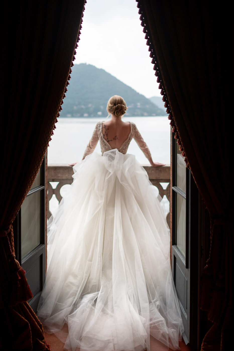 portrait of a bride from behind looking out from a luxurious balcony onto Lake Como at Villa Pizzo in Italy by Luxury wedding photographer in Italy Francesco Bognin