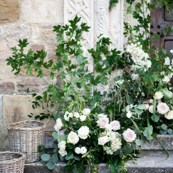 Stunning floral details pink roses baskets and greenery flanking an entrance at Castello di Tabiano in Parma Italy by luxury wedding photographer Francesco Bognin