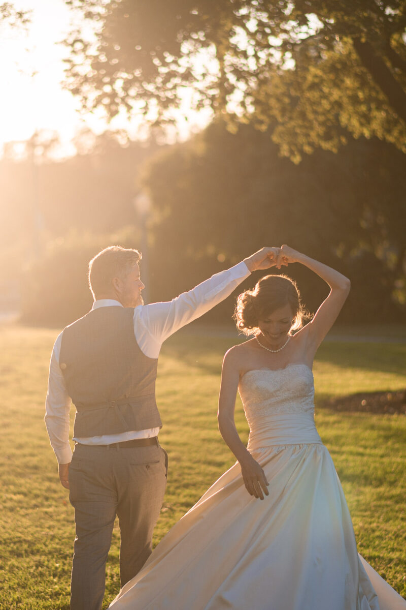 A groom spinning his smiling bride in a garden with the sunset in the distance in Pasadena Los Angeles California United States of America by destination wedding photographer Francesco Bognin
