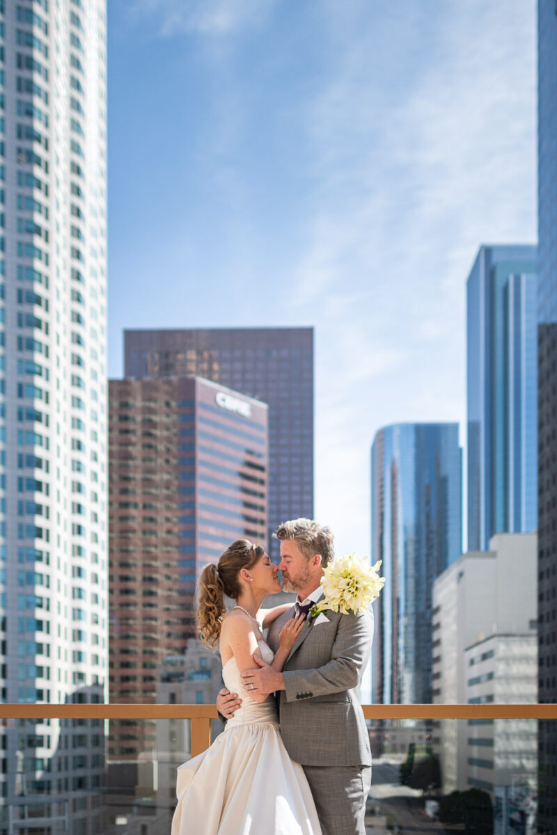 A bride and groom embracing on a balcony overlooking the dramatic skyline of Los Angeles in Pasadena California United States of America by destination wedding photographer Francesco Bognin