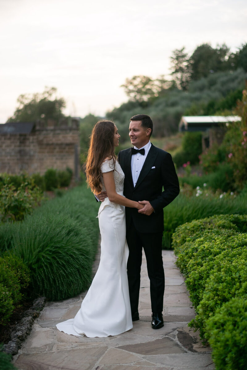 A bride and groom on a garden path hand in hand smiling as they look into each others eyes at Castello di Monterone in Perugia Umbria Italy by Luxury wedding photographer Francesco Bognin