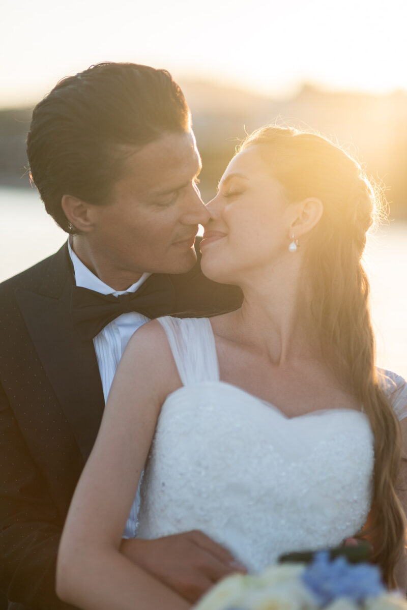 Bride and groom in an embrace and about to kiss with the sea and sun set behind them at Cala di volpe in Porto Cervo on the Emerald Coast of Sardinia by luxury wedding photographer italy Francesco Bognin