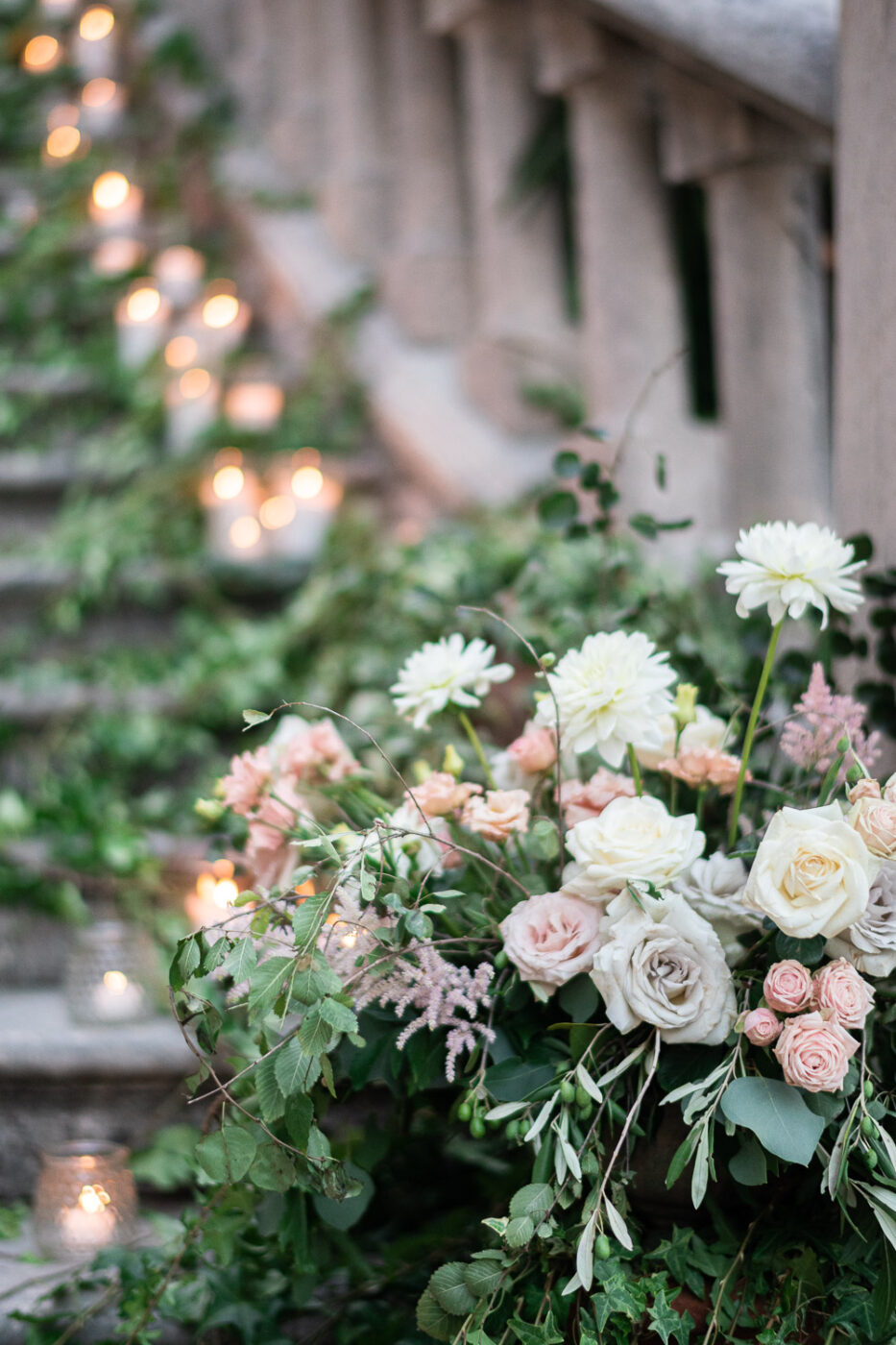 Floral arrangements and twinkling candles with ivy crawling up a historic castle staircase at CastelBrando in Treviso Italy by luxury wedding photographer Francesco Bognin