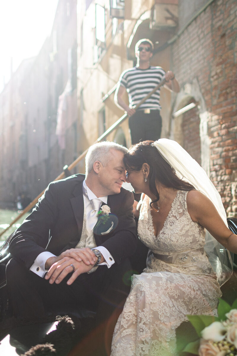 A beautiful bride and groom forehead to forehead on a gondola in the canals of venice with the sun behind them at Hotel Danieli in Venice Italy by luxury wedding photographer Francesco Bognin
