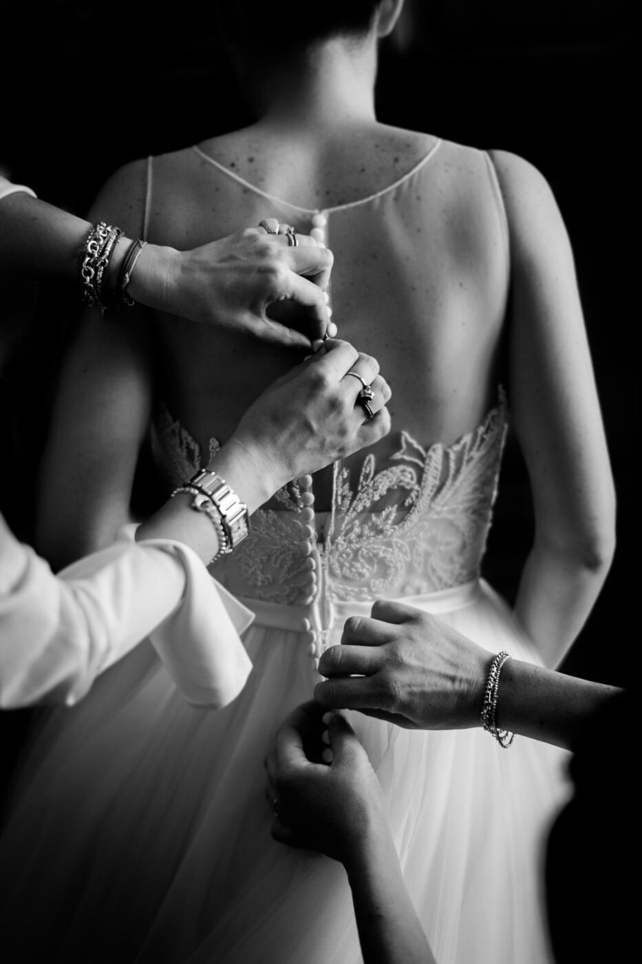 Black & White portrait of a bride from behind with 2 sets of hands closing the many buttons of her wedding gown in Verona Italy by Luxury Wedding Photographer Francesco Bognin