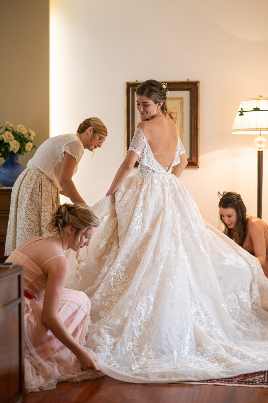 Candid moment of a bride looking behind over her shoulder with her dress open while being helped by her bridesmaids at Ristorante il Castello in Vicenza Veneto Italy by luxury wedding photographer Francesco Bognin