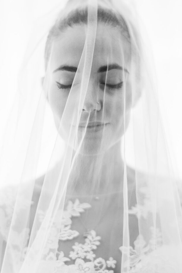 Beautiful blonde bride close up portrait with closed eyes and pierced nose under a veil in Italian wedding