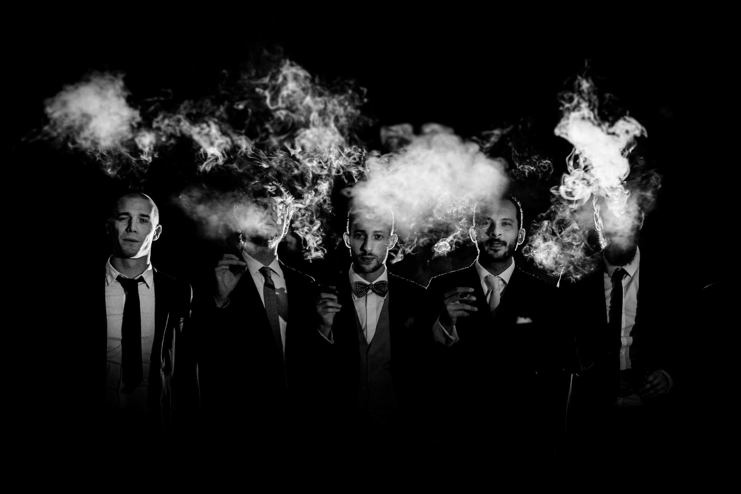 Fine art portrait in black and white of a groom and his groomsmen smoking and surrounded by clouds of smoke against an all black background shot by luxury wedding photographer Francesco Bognin