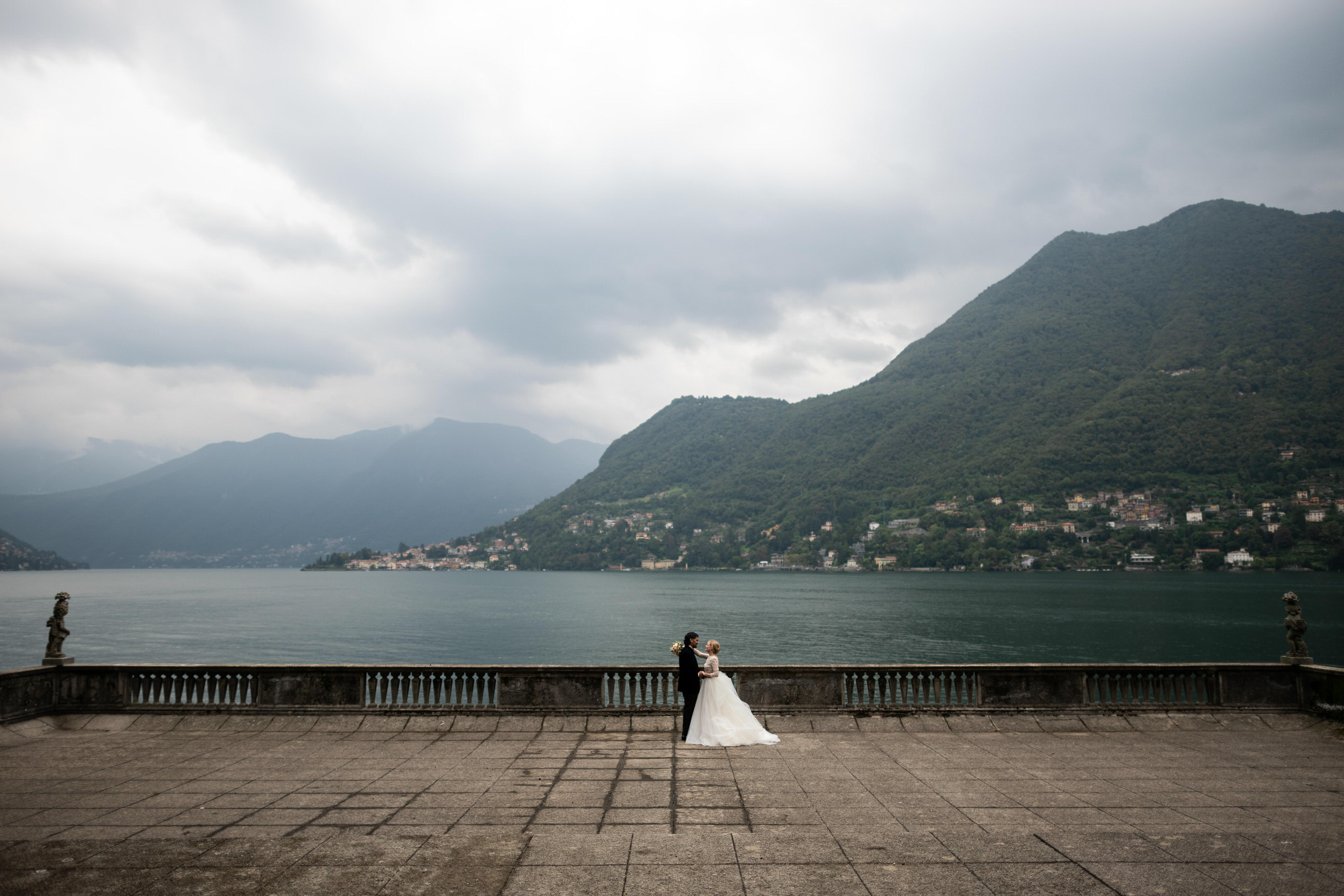 Cinematic portrait of a bride and groom from a distance on a terrace of Villa Pizzo with the hills and lake of Lake Como Italy in the background, shot by luxury wedding photographer Francesco Bognin