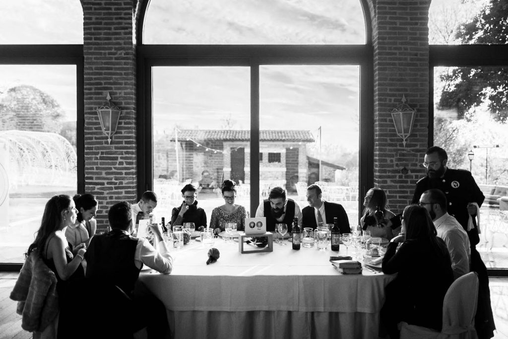 Luxury black and white reportage moment of a dinner with the bride and groom and a window placed symmetrically behind, distinctly reminicent of the last supper by Leonardo da Vinci shot by luxury wedding photographer Francesco Bognin