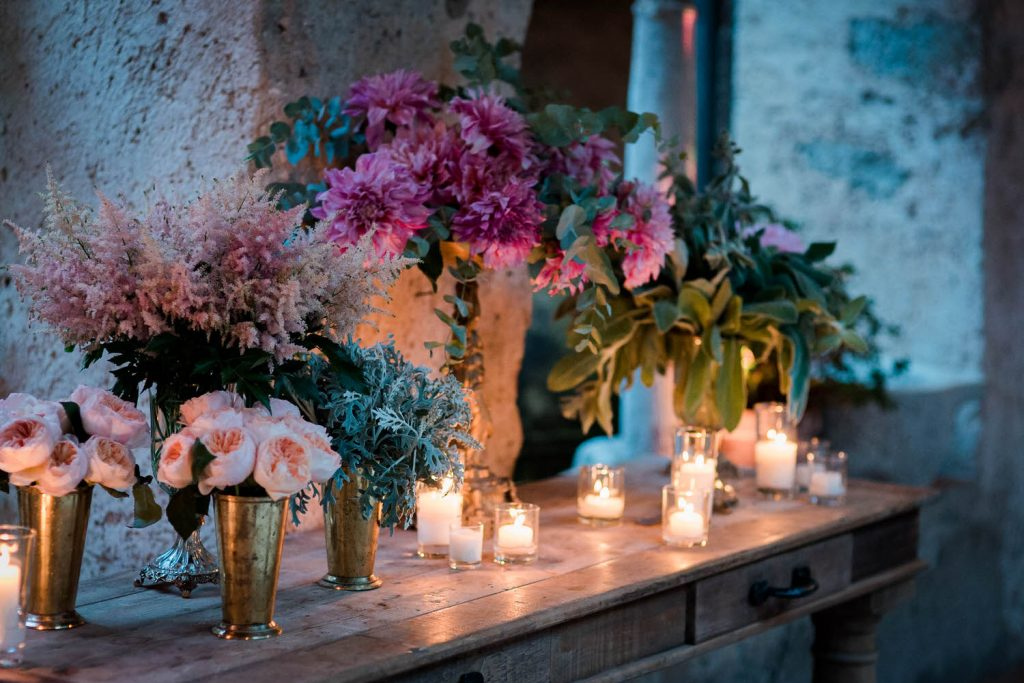 Pink and fuscia flowers glow from beneath thanks to many beautiful candles at Villa Cimbrone on the Amalfi Coast, planned by Brenda Babcock and shot by luxury wedding photographer Francesco Bognin
