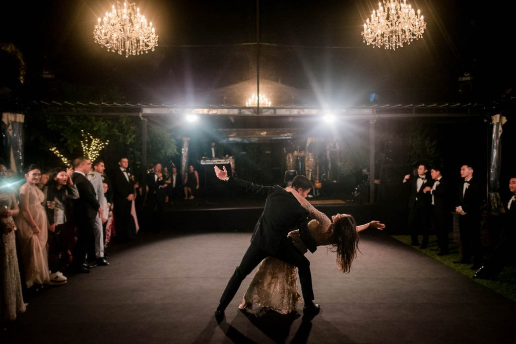 A groom dips his bride during their first dance under the light of chandeliers and surrounded by guests at edge of the dancefloor at the stunning Villa Cimbrone in Ravello on the Amalfi Coast of Italy, planned by Brenda Babcock and shot by luxury wedding photographer Francesco Bognin