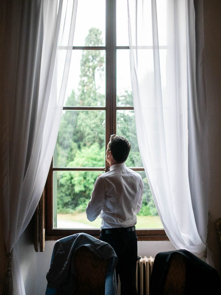 A groom looks out a window draped in white curtains and lit by natural light as he ties his tie in a beautiful room at Villa Ca Vendri in Verona Italy, shot by luxury wedding photographer Francesco Bognin