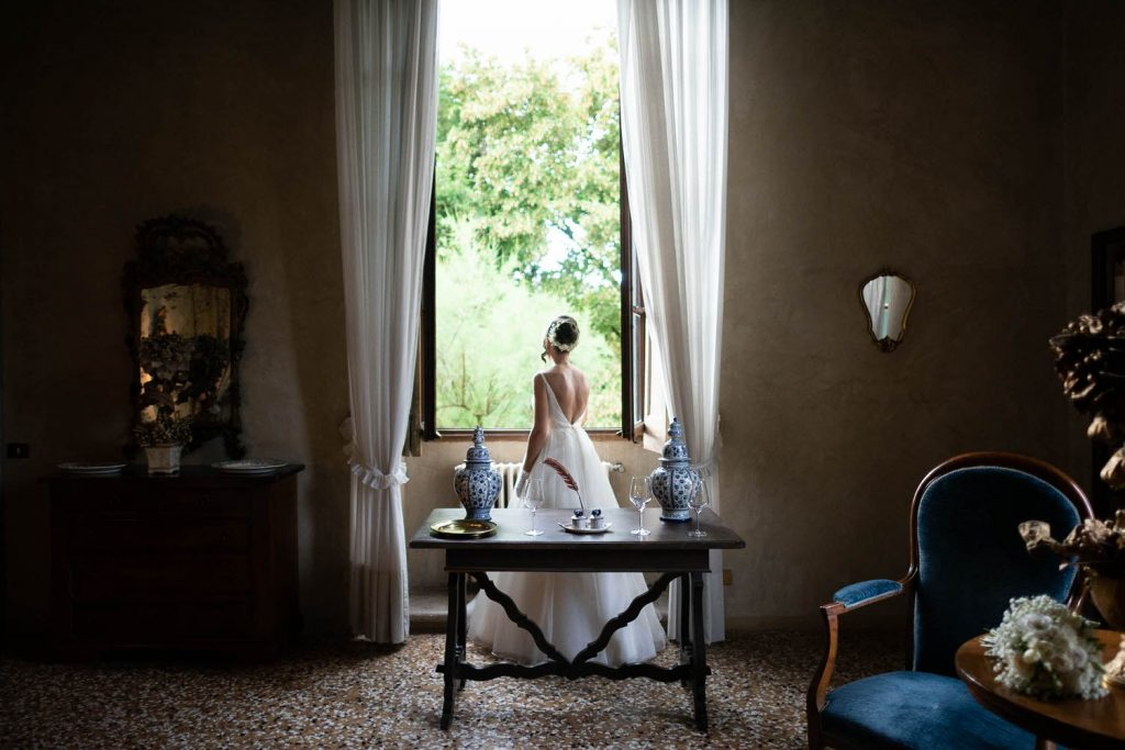 A lone bride in her wedding gown looks out a window as natural light pours in illuminating long white curtains and a beautiful villa room at Villa Ca Vendri in Verona Italy, shot by luxury wedding photographer Francesco Bognin