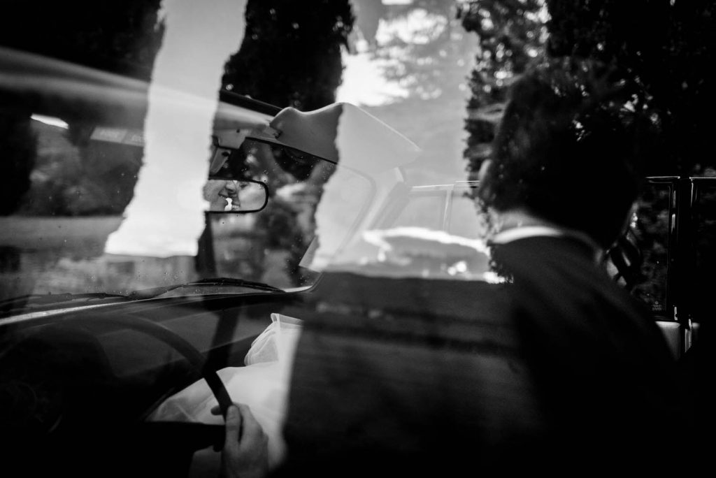 An artistic fine art black and white photo featuring multiple reflections including a kiss in the rear view mirror of the car, by luxury wedding photographer Francesco Bognin
