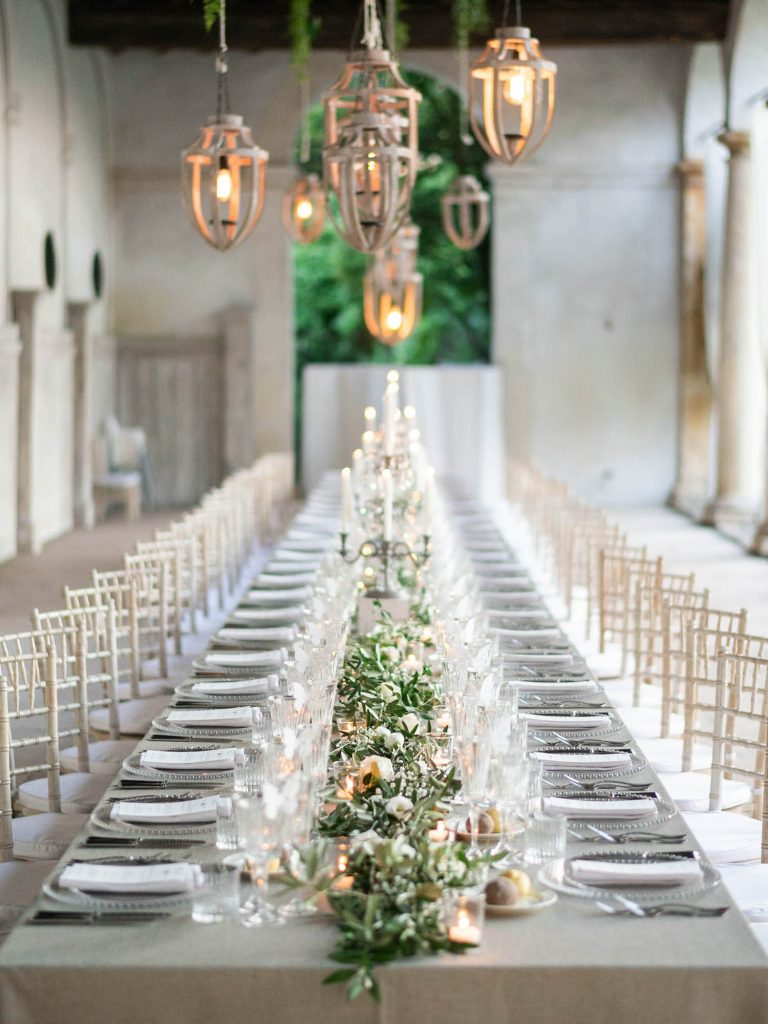 An elegant and modern imperial table set for a bridal dinner in clear glass an decorated in greens with white flowers and rustic but modern pendant lamps above at Villa Ca Vendri in Verona Italy, by luxury wedding photographer Francesco Bognin