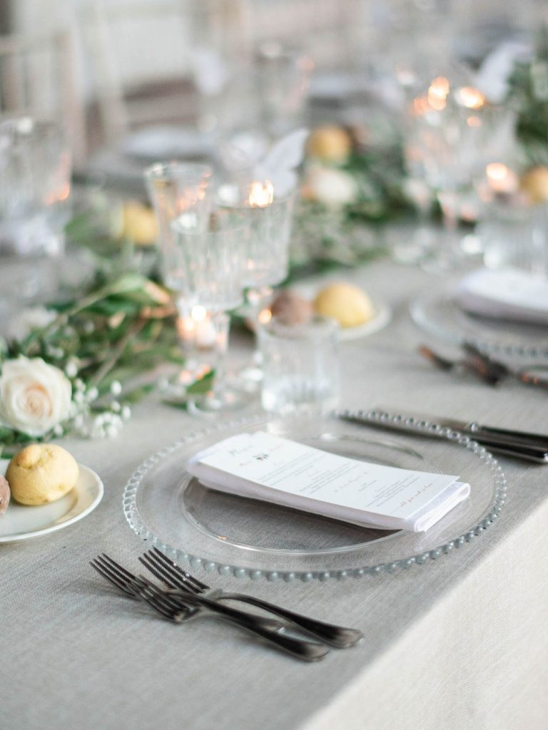 An elegant and modern imperial table set for a bridal dinner in clear glass an decorated in greens with white flowers and showing the menu at Villa Ca Vendri in Verona Italy, by luxury wedding photographer Francesco Bognin