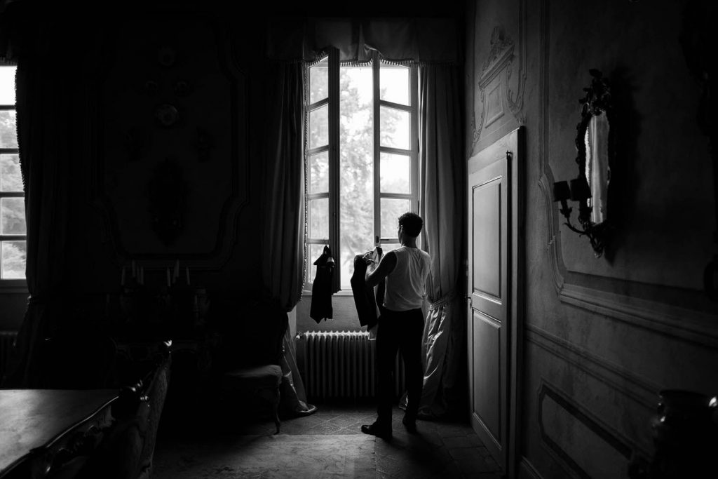 A black and white fine art reportage moment showing a groom getting ready against the natural light of a window in an otherwise dark villa room in Italy, shot by luxury wedding photographer Francesco Bognin