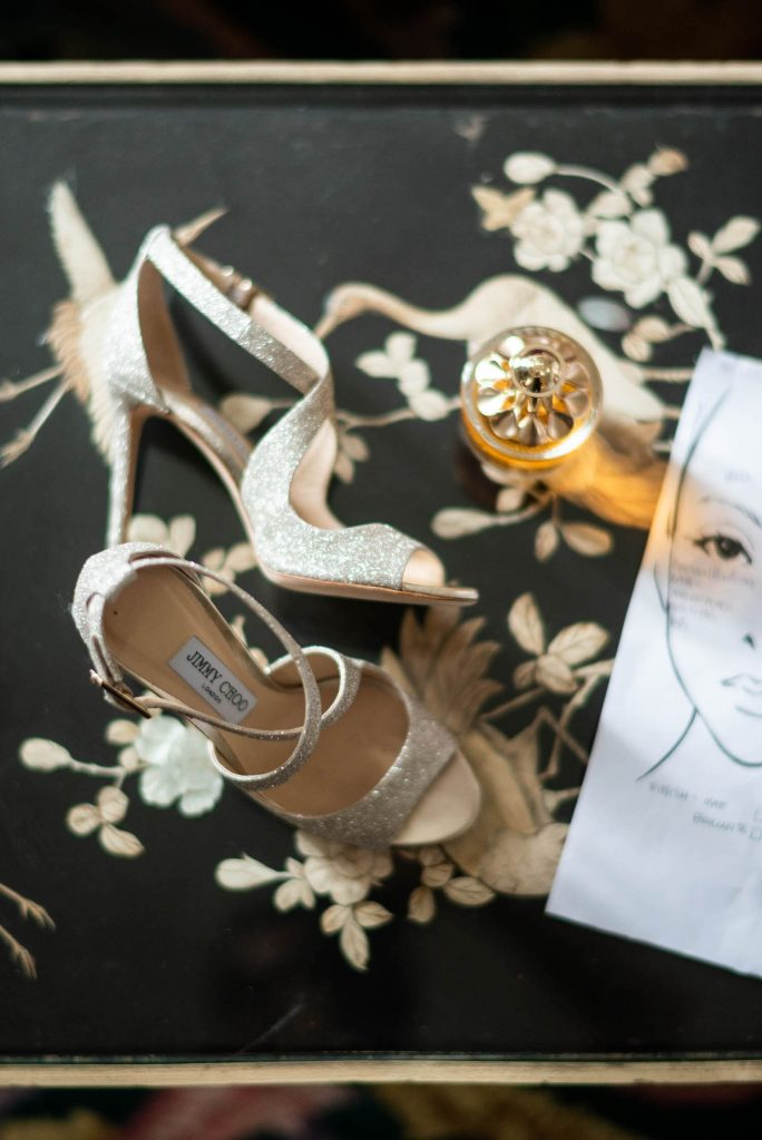 Strapped golden metallic glittering bridal sandals by Jimmy Choo rest against a black and gold floral setting and next to a makeup illustration in an Italian villa wedding, shot by luxury wedding photographer Francesco Bognin