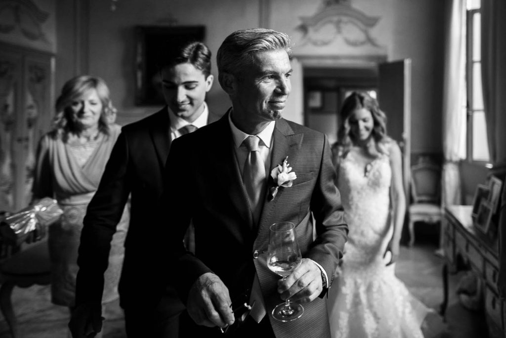 A father of the bride walks proudly with his face turned to the side toward natural light, wearing a suit and a half smile and followed by family members including the happy bride who looks down as she walks through an Italian Villa, by luxury wedding photographer Francesco Bognin
