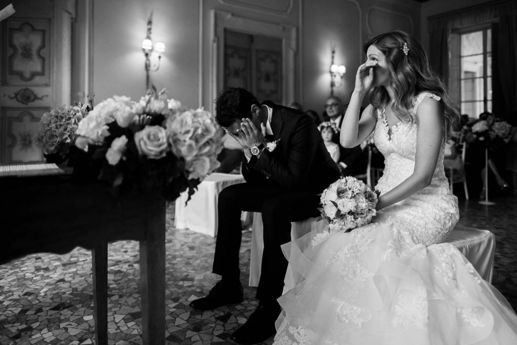 An emotional black and white photo showing a bride and groom each with their hands to their faces as they wipe away their tears during an emotional ceremony in an Italian Villa wedding, she holding her bouquet, by luxury wedding photographer Francesco Bognin