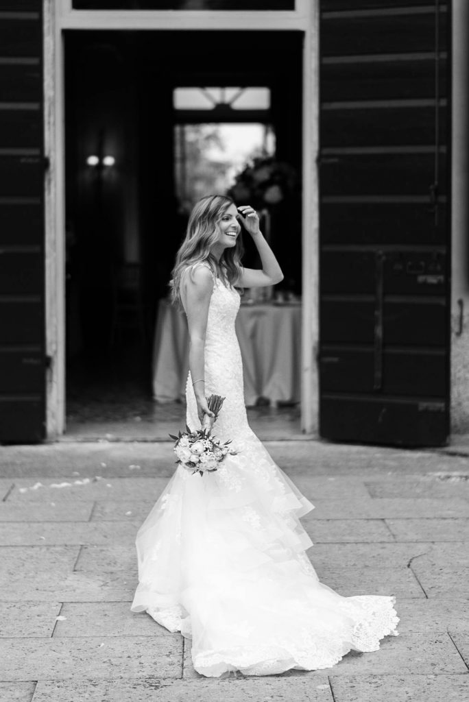 A bride stands in her gown with her bouquet in one hand falling to her side and her other hand adjusting her hair as she smiles and looks into the distance in front of an Italian Villa, by luxury wedding photographer Francesco Bognin