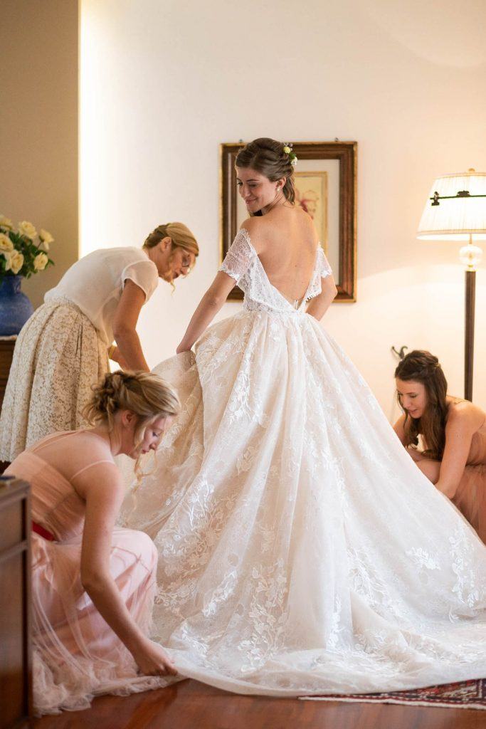 A bride as seen from behind looks over her shoulder and down as she is surrounded by her bridal party during her getting ready, with the back of her dress still unbuttoned, by luxury wedding photographer Francesco Bognin