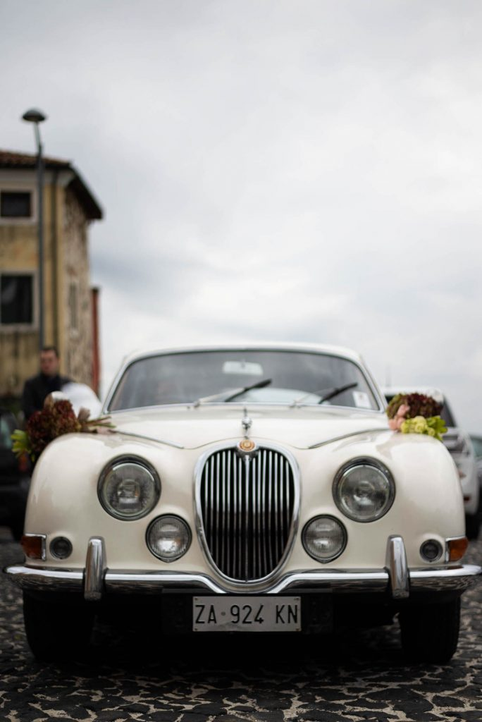 A classic Rolls Royce faces us head on with the sky in the background, by luxury wedding photographer Francesco Bognin