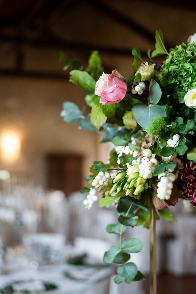 A bouquet of flowers enters the photo on the right, in pink green and white, with table settings in the background, by luxury wedding photographer Francesco Bognin