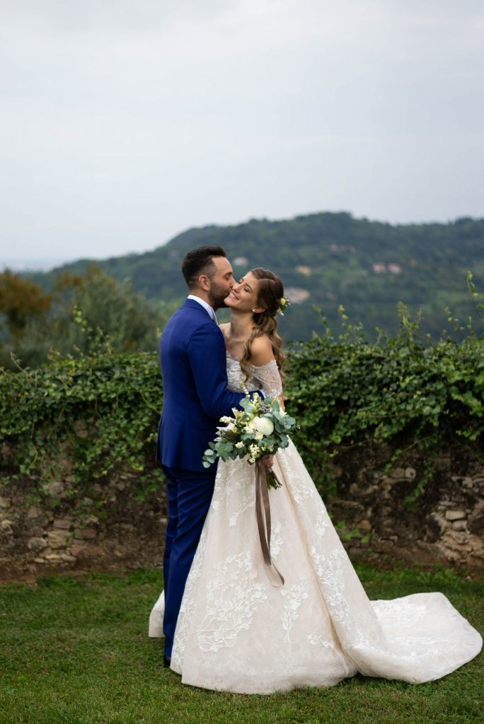 A bride receives a kiss on her cheek from her groom and they share an embrace, she holding her bouquet, while they stand in a garden setting with Italian hills in the background, by luxury wedding photographer Francesco Bognin