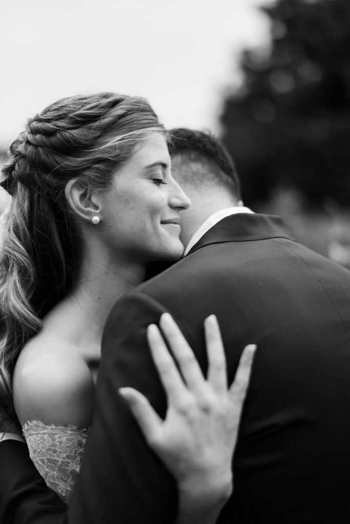 A close up portrait in black and white of a bride and groom in embrace, showing a smiling bride with closed eyes, by luxury wedding photographer Francesco Bognin