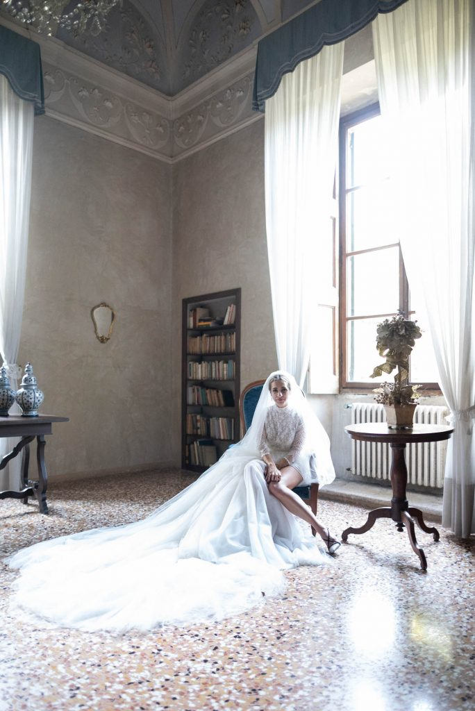 A chic bride sits in a chair bathed in natural light and surrounded by her dress, with her leg peeking out from the generous slit in her dress, set in a villa room at Villa Ca Vendri in Verona Italy, by luxury wedding photographer Francesco Bognin