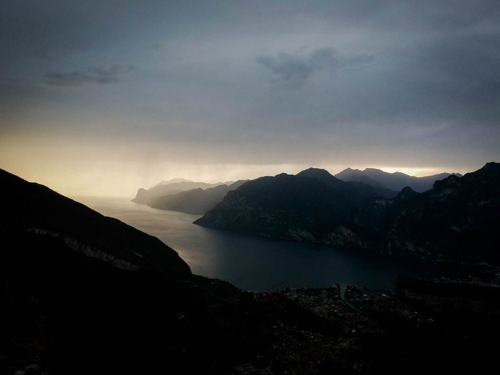 A moody and dark photo of Lake Garda in Trento on a rainy day, with clouds . overhead and the sunset glowing just under the clouds and along the far reaches of the lake, by luxury wedding photographer Francesco Bognin