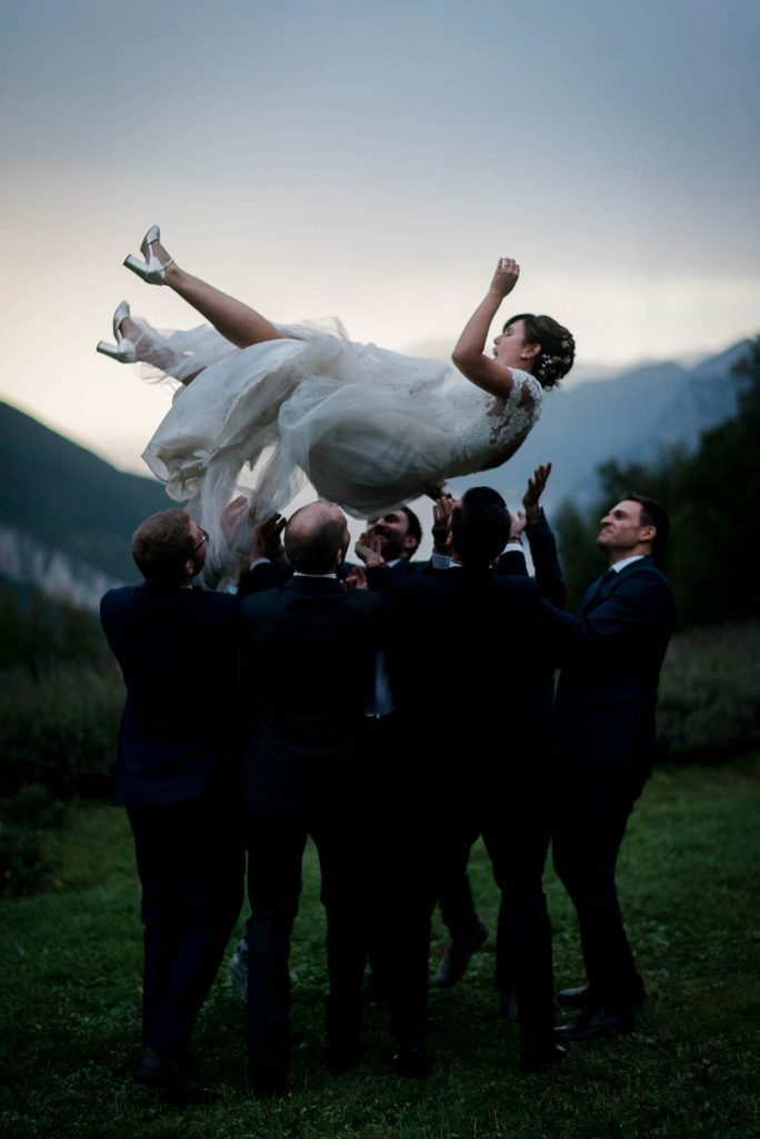 A bride is tossed in the air by her groom and groomsmen on a rainy day in Trento along Lake Garda in Italy, by luxury wedding photographer Francesco Bognin