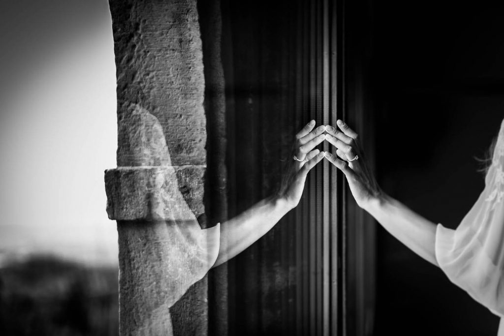 The hand of a bride skims a window delicately and her reflection creates a beautiful symmetry in black and white by luxury wedding photographer Francesco Bognin