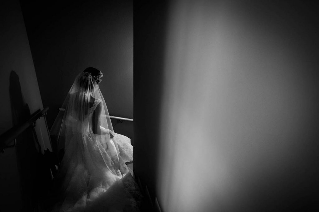 A bride as seen from above and behind descends a dimly lit staircase in Italy, by luxury wedding photographer Francesco Bognin