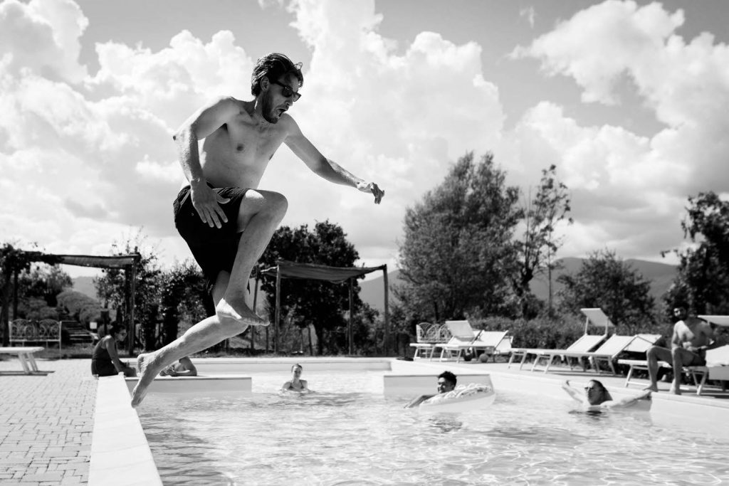 A black and white photo showing a man mid-leap as he jumps into a pool where others are already resting along the edges in the water, by luxury wedding photographer Francesco Bognin