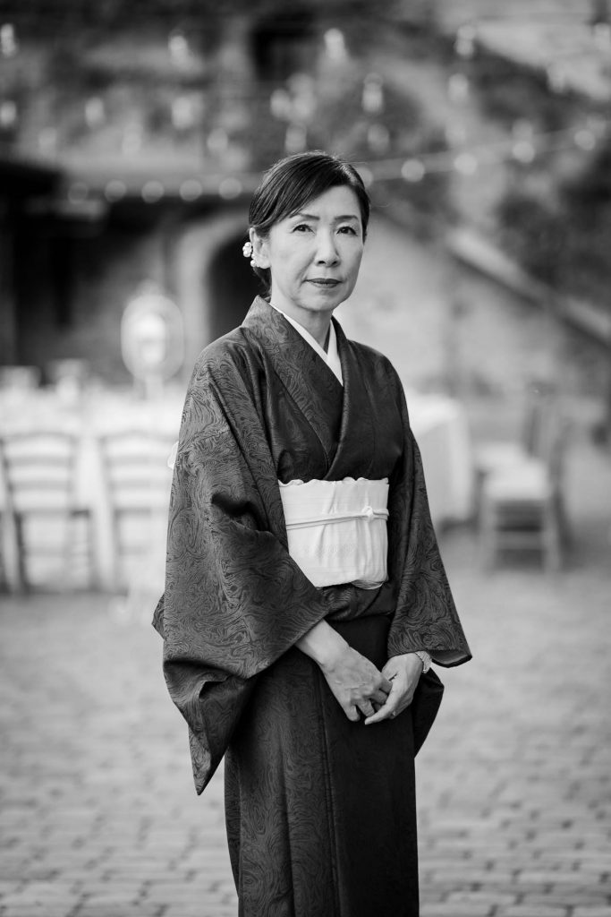 A somber black and white portrait of a mature woman wearing a kimono at a wedding ceremony in Italy, by luxury wedding photographer Francesco Bognin