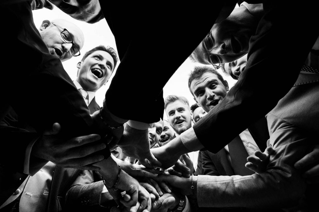 A huddle of men as seen from below their outstretched hands that meet in the middle, with their happy and expressive faces seen from above, by luxury wedding photographer Francesco Bognin