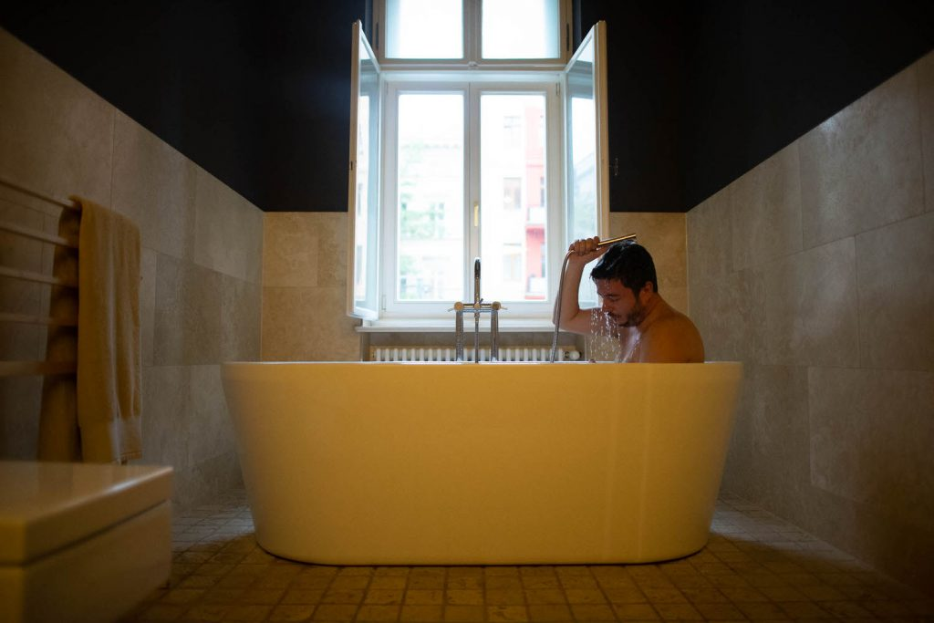 A groom bathes in a yellow bathtub and showers his head in water before his wedding in Italy, by luxury wedding photographer Francesco Bognin