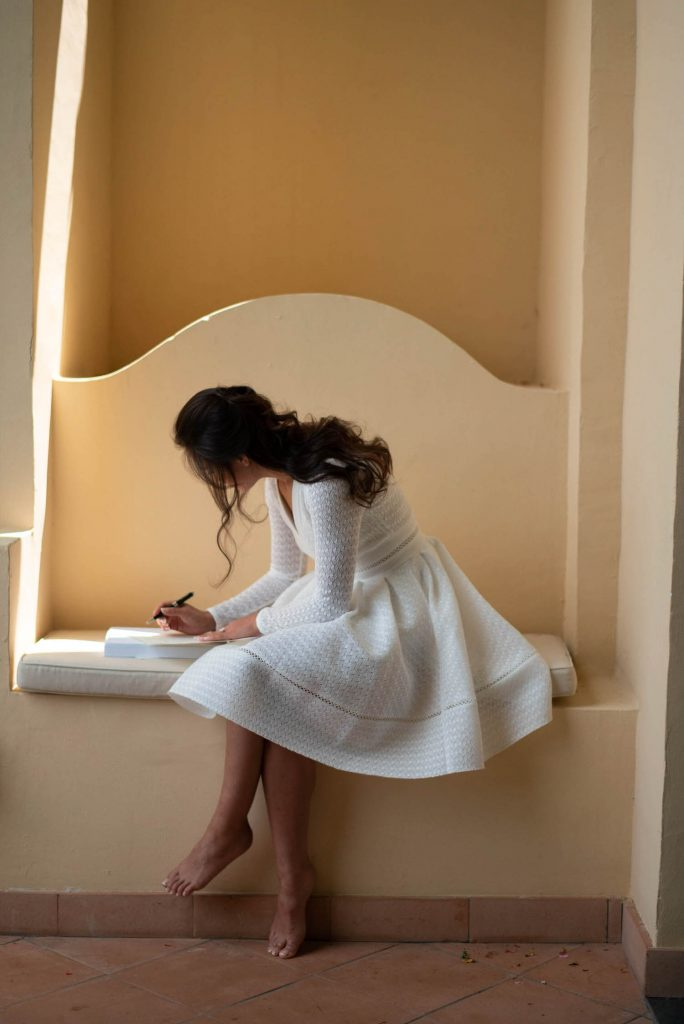 A barefoot bride wearing a white day dress sits in a hidden corner of Belmond Hotel Caruso in Ravello as she writes her vows and her hair tumbles down her back and along her face, by luxury wedding photographer Francesco Bognin