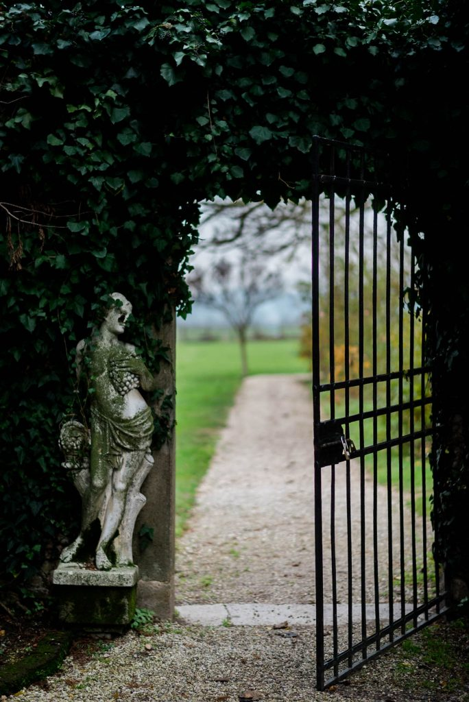A gate and statue stand in a garden marking a path within a historic Italian Villa, by luxury wedding photographer Francesco Bognin