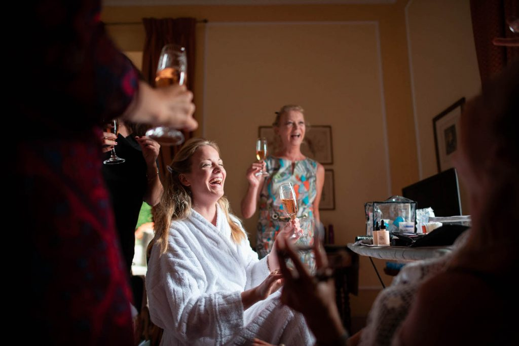 A bride in a robe laughs heartily as her bridesmaids hold up glasses of wine in a toast while she gets ready at Villa Pizzo on Lake Como in Italy, by luxury wedding photographer Francesco Bognin