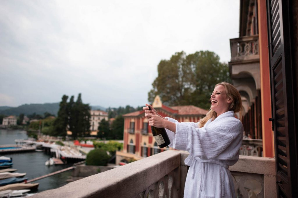 A bride in a robe stands on her balcony and opens a bottle of champagne with a look of joy and excitement on . her face, and the buildings surrounding . lake Como visible in the background, by luxury wedding photographer Francesco Bognin