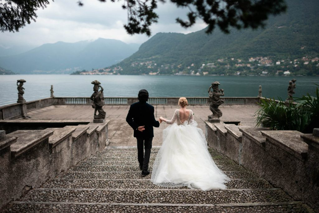 A bride and groom descend stairs hand in hand, with her ample tulle skirt trailing behind and the hills and waters of Lake Como in the background at Villa Pizzo by luxury wedding photographer Francesco Bognin