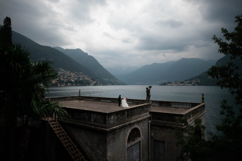 A bride and groom as seen from a distance as they stand on a rooftop terrace of Villa Pizzo on the shores of lake Como with the hills and clouds in the distance, by luxury wedding photographer Francesco Bognin