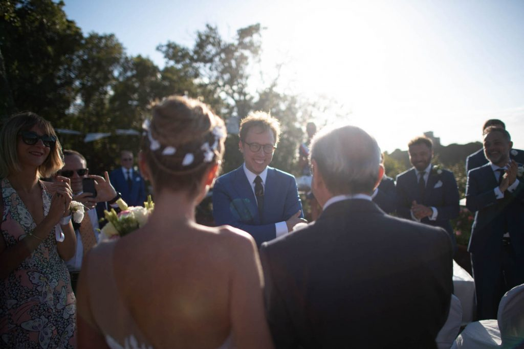 A groom stands smiling with arms crossed under the glow of natural light as he looks toward his bride, who approaches with her father, as see from behind the bride, In a private villa in Italy, by luxury wedding photographer Francesco Bognin