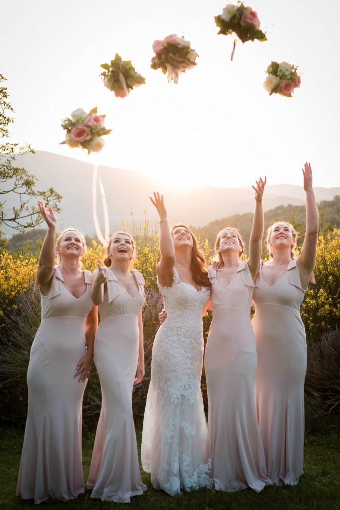 A bride and her bridesmaids stand in a line with their arms and faces pointed to the sky as they watch five bouquets fly above them in a parabolic shape after being thrown to the sky, by luxury wedding photographer Francesco Bognin