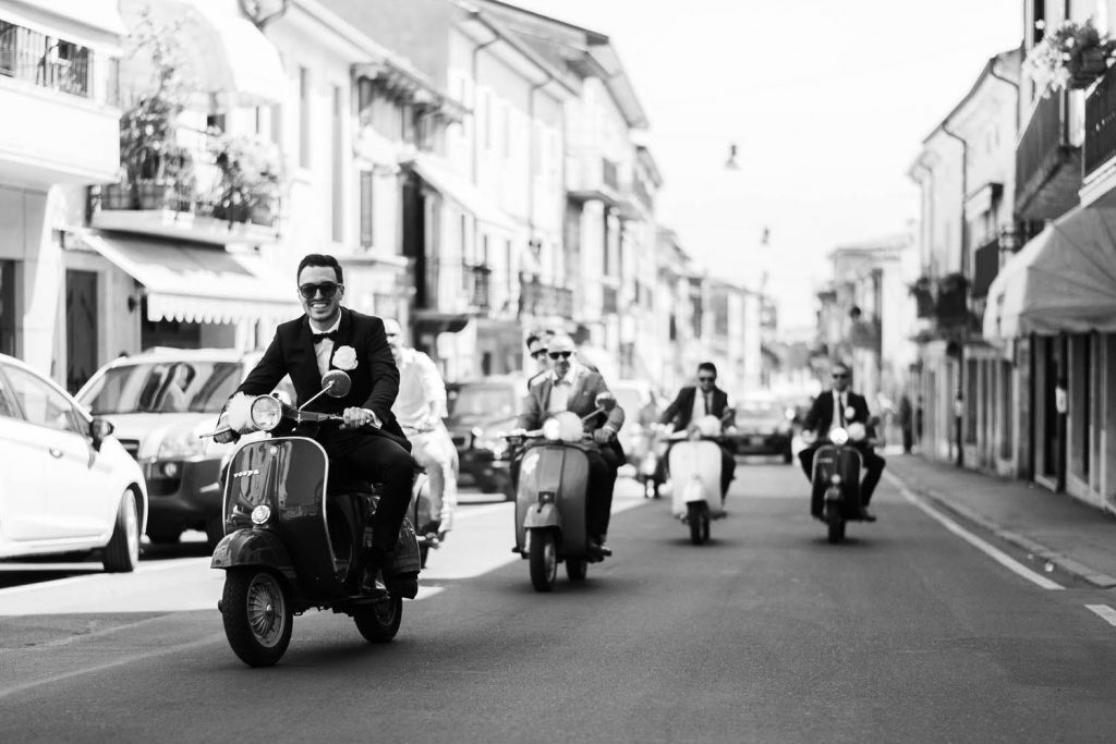 A black and white photo showing a groom in his tuxedo and sunglasses riding a vespa with his groomsmen riding behind him on vespas along the streets of Procida off the coast of Naples Italy, by luxury wedding photographer Francesco Bognin